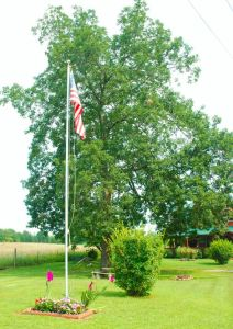 The Flag Pole is located in the center of the yard and visible to anyone entering the drive.